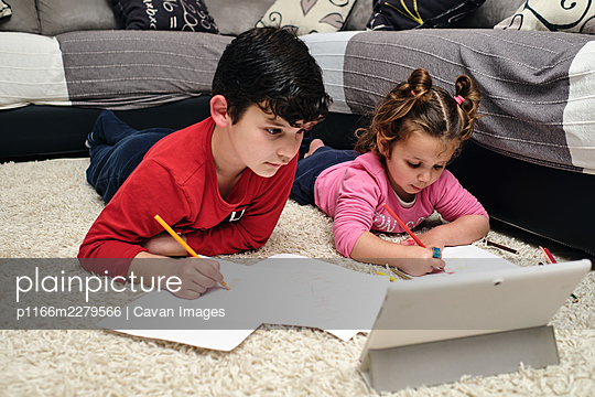 children painting a picture while receiving instructions on the tablet - p1166m2279566 by Cavan Images