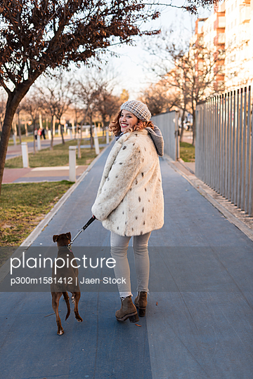 Happy young woman going walkies with her dog - p300m1581412 von Jaen Stock