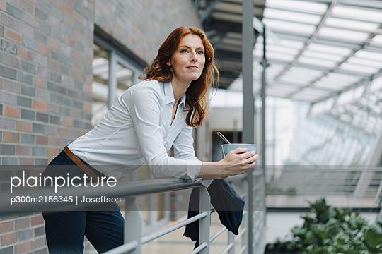 Businesswoman having a break eating muesli in a modern office building - p300m2156345 by Joseffson