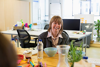 Portrait smiling, confident businesswoman eating in office - p1023m2017193 by Martin Barraud