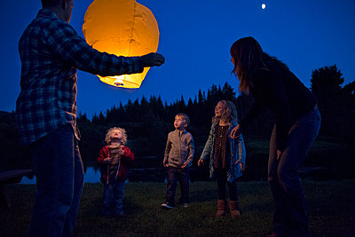 Low angle view of happy family with illuminated lantern at field - p1166m1095816f by Cavan Images