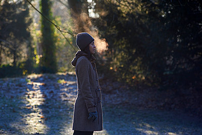 Side profile of Asian woman enjoying the cold weather blowing mist - p1166m2112882 by Cavan Images