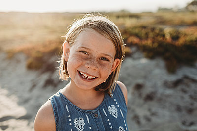 Portrait of young school age girl with freckles smiling on beach - p1166m2165870 by Cavan Images