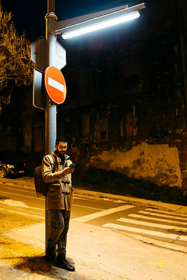 Spain, Igualada, man standing under a street lamp at night using cell phone - p300m2080709 by Josep Rovirosa