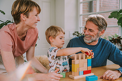 Mother and father playing with son toy block puzzle at home - p300m2226227 by Mareen Fischinger