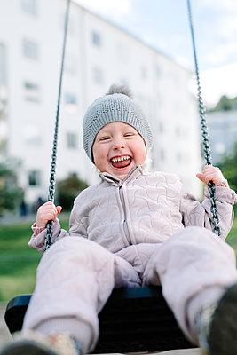 Boy having fun on swing in playground - p312m1131406f by Malin Morner