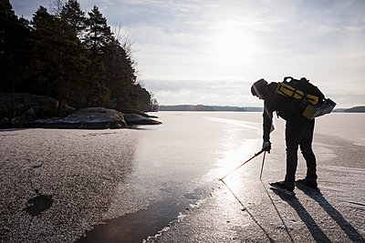 Full length of man dipping hiking pole in water while standing on frozen lake - p426m1407362 by Katja Kircher