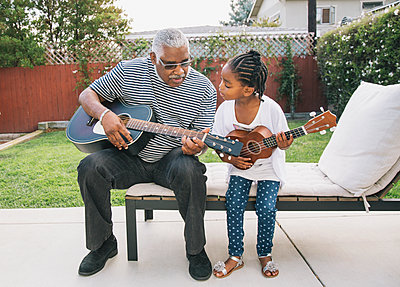 African American grandfather teaching granddaughter to play guitar - p555m1408330 by Hello Lovely