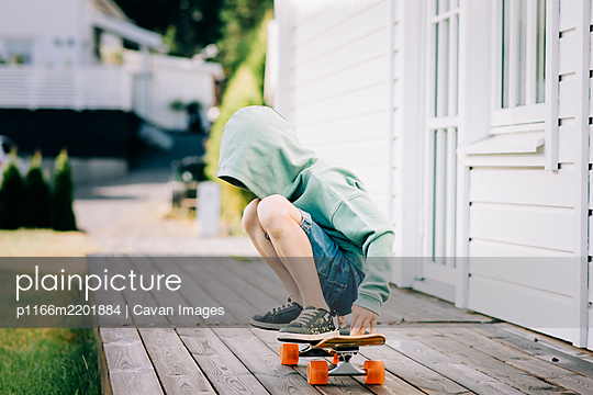boy sat on a skateboard with his hood up hiding his face - p1166m2201884 by Cavan Images