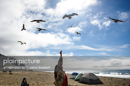 Woman holds chip as seagulls fly overhead - p1166m2201907 by Jaime Boddorff