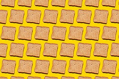 Pattern of slices of wheat bread against yellow background - p300m2198281 by Gemma Ferrando