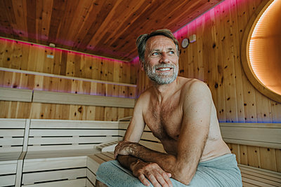 Smiling mature man looking away while sitting at finnish sauna - p300m2266786 by Mareen Fischinger