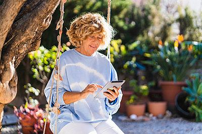 Mature woman using digital tablet while sitting on swing at back yard - p300m2276077 by Manu Padilla Photo
