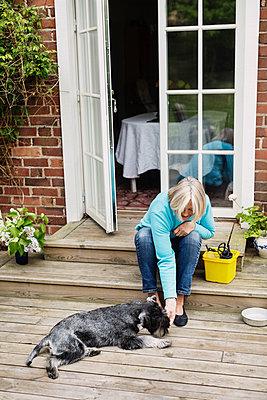 Senior woman stroking dog lying at house entrance - p426m1114785f by Maskot