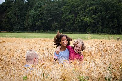 Kinder spielen auf Feld mit Gerste - p471m2022072 von CLMasur