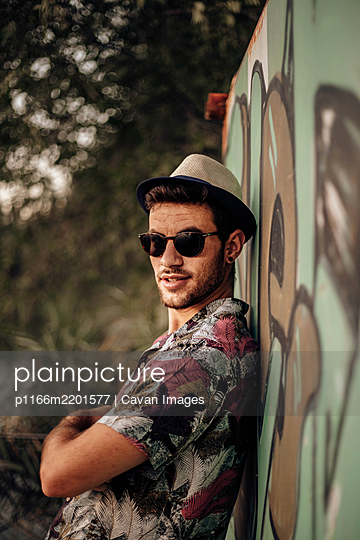 Handsome guy smiling and posing with crossed arms and sunglasses - p1166m2201577 by Cavan Images
