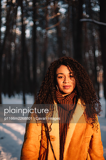 Portrait of young woman standing in park in winter during sunny day - p1166m2268801 by Cavan Images