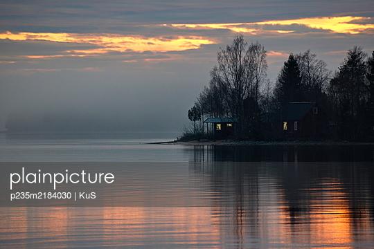 Licht leuchtet im Fenster einen kleinen Häuschens auf einer Insel bei Sonnenuntergang - p235m2184030 von KuS