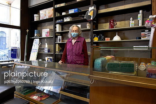 Old saleswoman with mouth protection in her shop - p267m2260769 by Ingo Kukatz