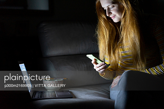 Young woman sitting on the couch at home using laptop and smartphone - p300m2169909 by VITTA GALLERY
