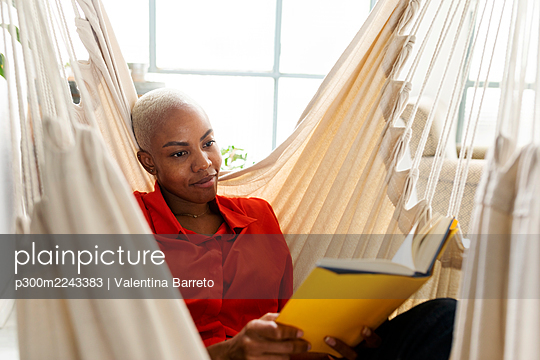 Woman sitting in hammock reading book - p300m2243383 by Valentina Barreto