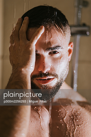 Shirtless handsome young man taking shower in bathroom at home - p300m2256293 by Miguel Frias