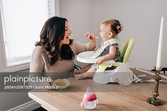 Mother feeding baby daughter in child seat on kitchen table - p924m2097328 by Sara Monika