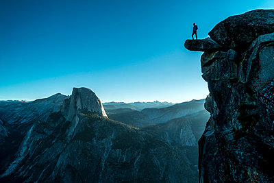 Low angle view of man standing on mountain at Yosemite National Park against clear blue sky - p1166m1415096 by Cavan Images