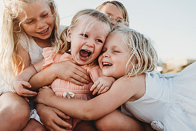 Close up of toddler laughing surrounded by young sisters - p1166m2165876 by Cavan Images
