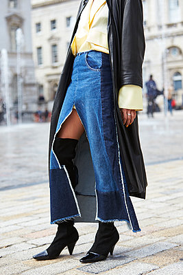 Woman in long denim skirt and leather coat, low section - p1407m1545428 by Guerrilla
