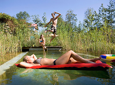 Austria, Salzburger Land, Teenagers (14-15) at garden pool, having fun - p30016613f by Wolfgang Weinhäupl
