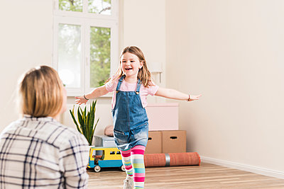 Happy girl running towards mother in empty apartment - p300m1460588 by Uwe Umstätter