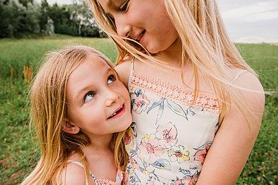 Two little sisters cuddling on a meadow - p300m2069661 by Nicole Matthews