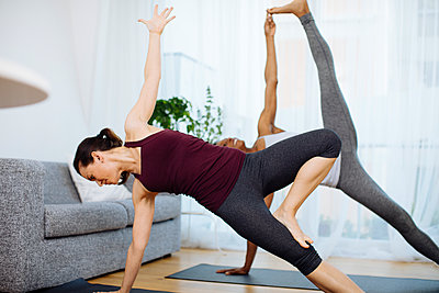 Two women practicing yoga at home - p300m2121881 by Sofie Delauw