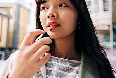 Young woman with long hair applying lip gloss - p300m2298979 von Angel Santana Garcia