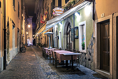 Italy, Trentino-Alto Adige, Riva del Garda, Restaurant by night - p300m937539 by Val Thoermer