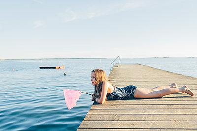 Sweden, Blekinge, Karlskrona, Salto, Girl (10-11) lying on pier and fishing - p352m1187363 by Karin Enge Vivar
