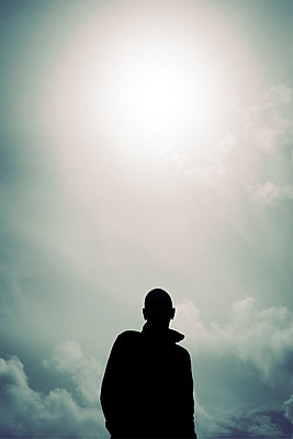 Silhouette of man against bright sun and cloudy sky - p597m2186047 by Tim Robinson
