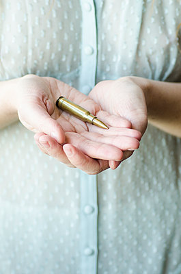 Woman holding a bullet  - p794m1026550 by Mohamad Itani
