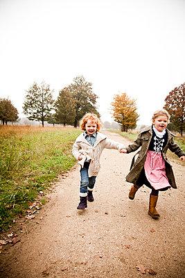 Zwei Schwestern laufen Hand in Hand - p904m741732 von Stefanie Päffgen