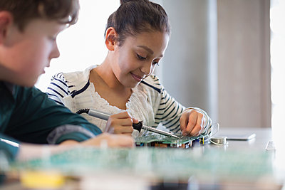 Students soldering circuit board in classroom - p1023m1506416 by Martin Barraud