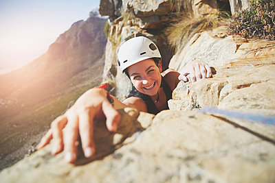 Portrait smiling, confident rock climber reaching for rock - p1023m1561183 by Trevor Adeline