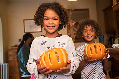 Portrait happy brother and sister holding pumpkins - p1023m2187703 by Sam Edwards