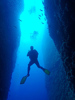 Scuba diver while diving in canyon - p1166m2136959 by Cavan Images