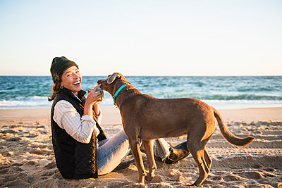 Young woman enjoying drink in mug while beach car camping with dog - p1166m2285584 by Cavan Images