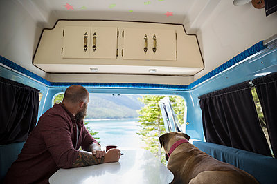 Man and dog sitting at table in the back of camper van at lakeside - p1192m1184069 by Hero Images