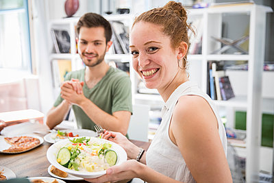 Young woman is smiling at camera with salad bowl in her hands - p276m2110680 by plainpicture