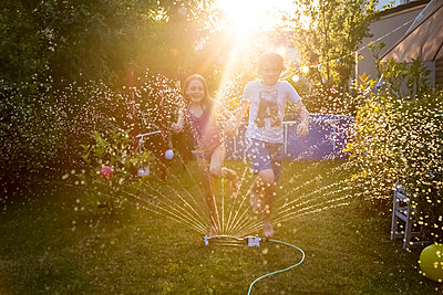 Brother and sister having fun with lawn sprinkler in the garden - p300m2023762 by Sandra Roesch