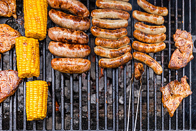 Different meat, maize and fried sausages on barbecue grill - p300m2024211 by Tom Chance