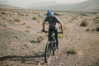 Spain, Lanzarote, mountainbiker on a trip in desertic landscape - p300m2102592 by Hernandez and Sorokina